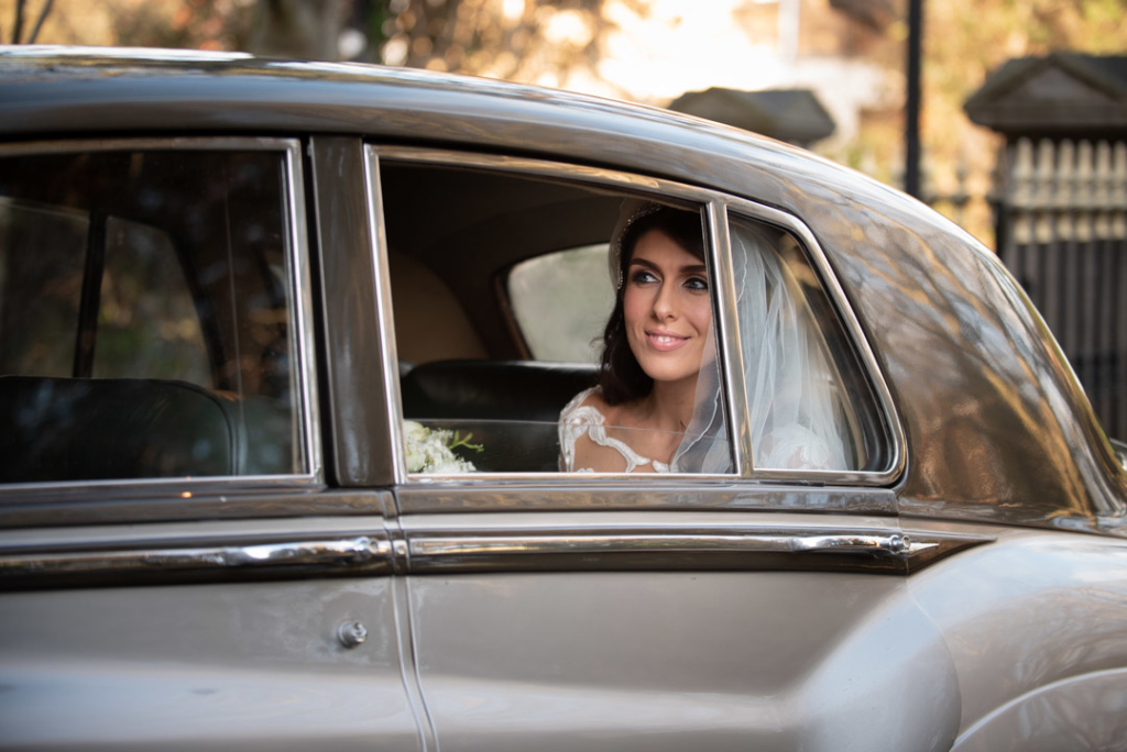 Bride in the back of wedding car arriving at Church