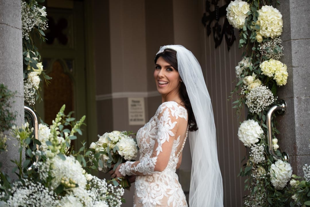 Bride smiling looking back over shoulder at the door of the Church