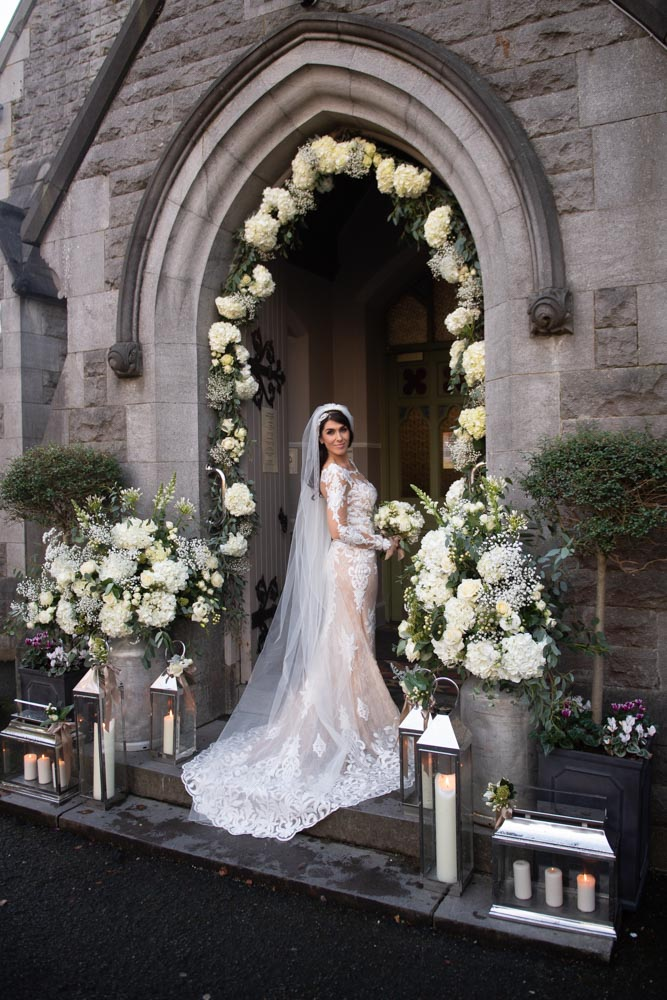 Bride standing at the Church door surrounded by flower arch and candles