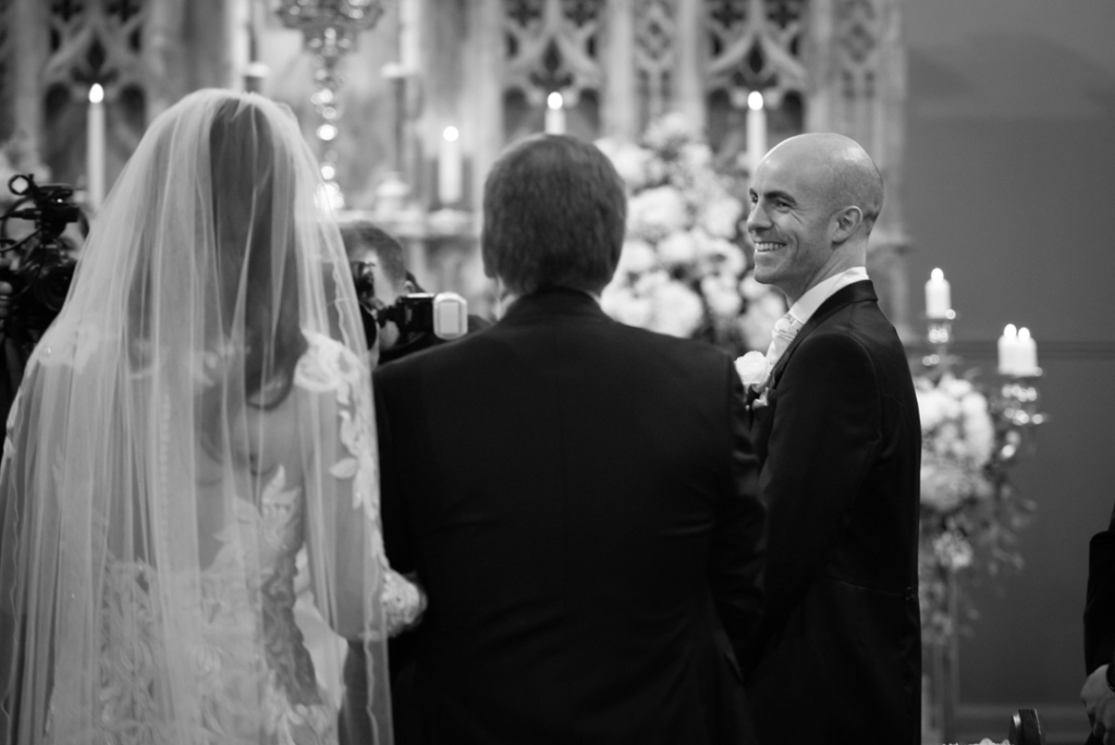 Groom smiling at Bride walking down the aisle with her dad