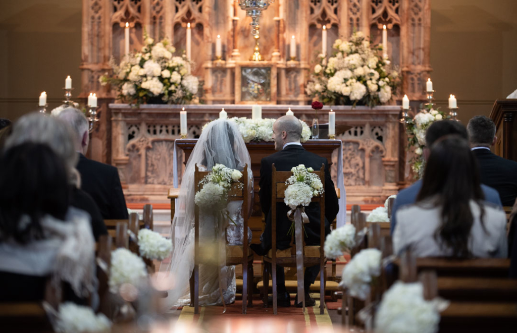Bride and groom sitting at the top of the aisle with white hydrangea flowers on the chairs
