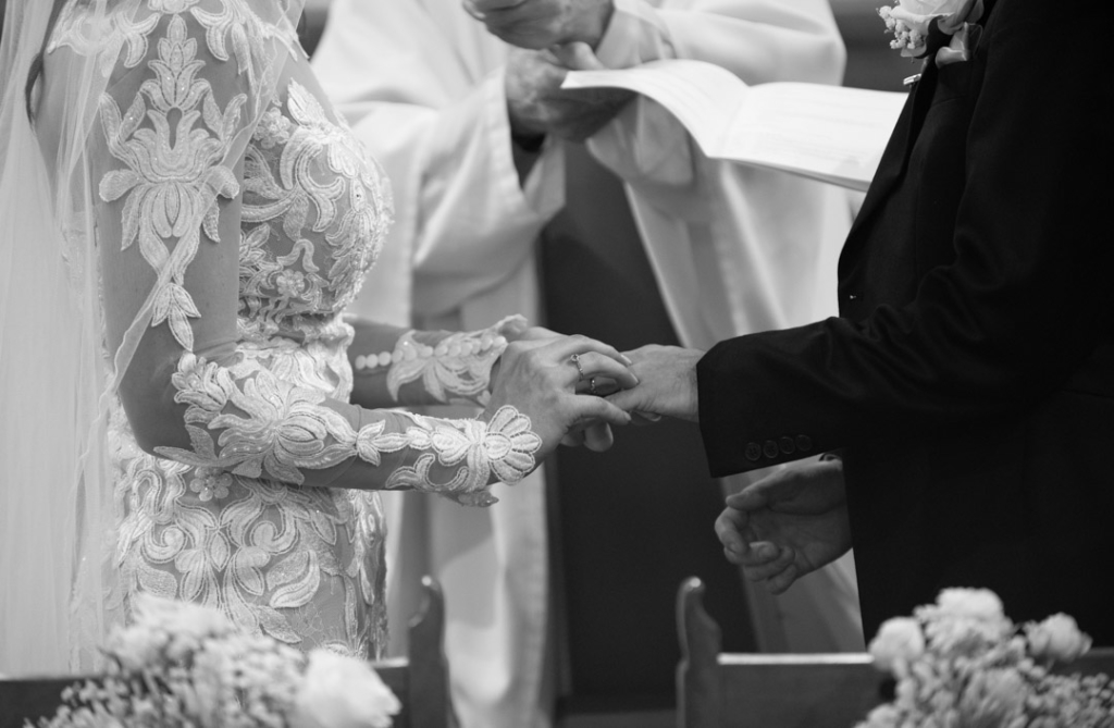 Bride placing the wedding ring on the grooms hand
