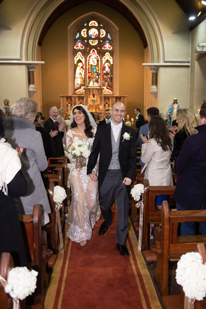 Bride and groom walking down the aisle after getting married