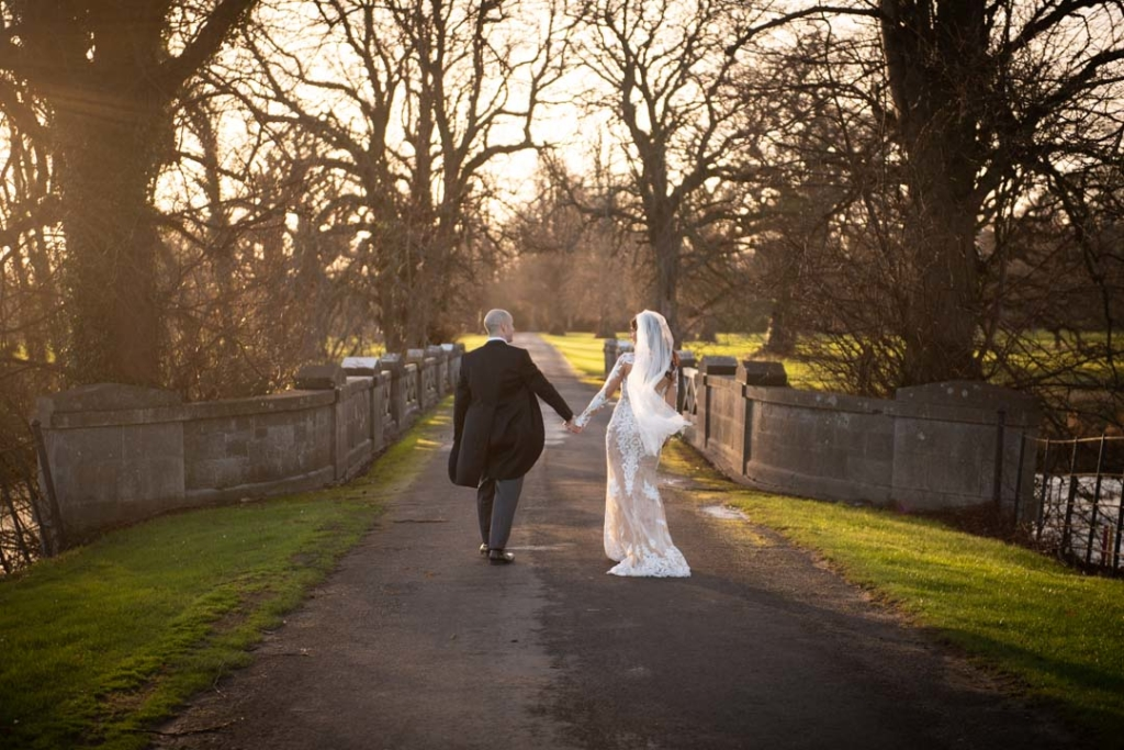 Bride and groom walking over bridge holding hands at Luttrellstown Castle