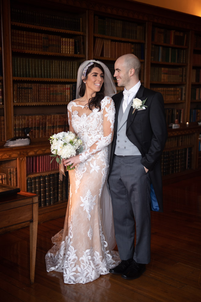Bride and groom laughing with each other in the library at Luttrellstown Castle