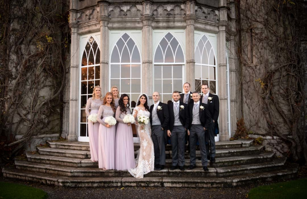 Bride and groom standing with their bridal party outside Luttrellstown Castle