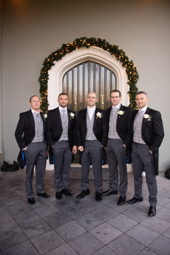 Groom and groomsmen standing outside the front door at Luttrellstown Castle