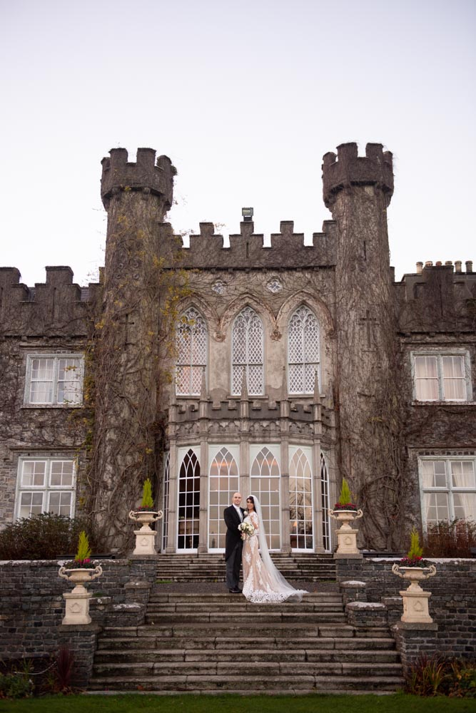 Bride and groom standing outside on the steps of Luttrellstown Castle
