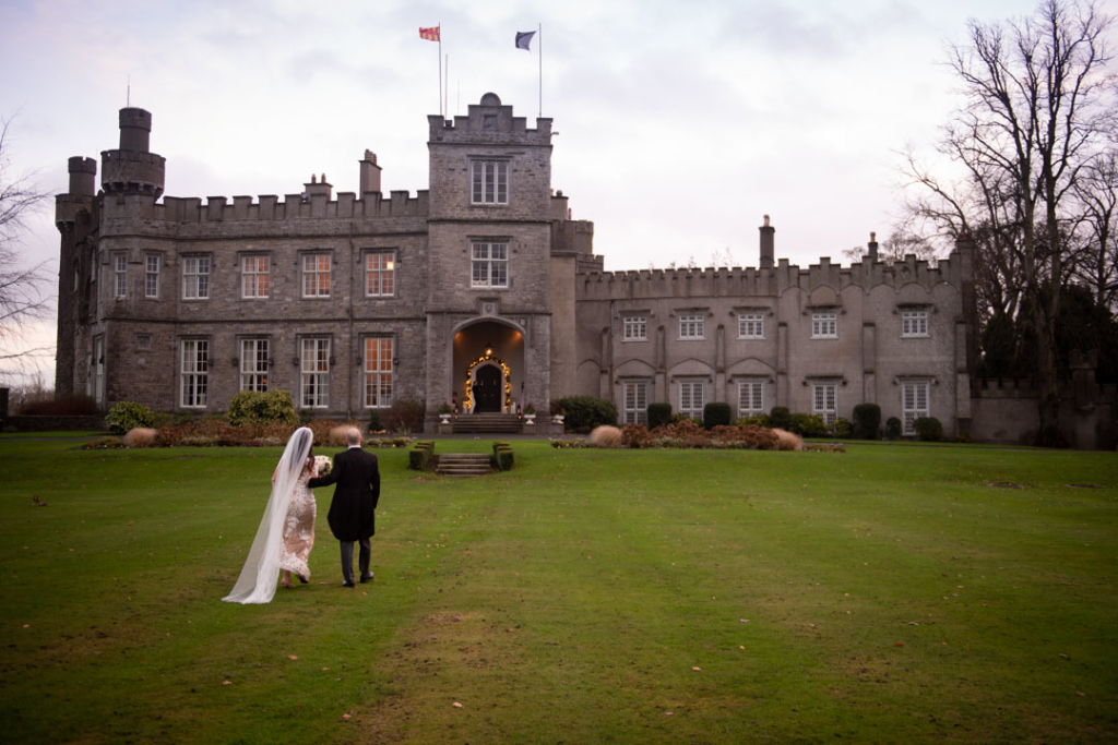 Bride and groom walking on the grass towards Luttrellstown Castle