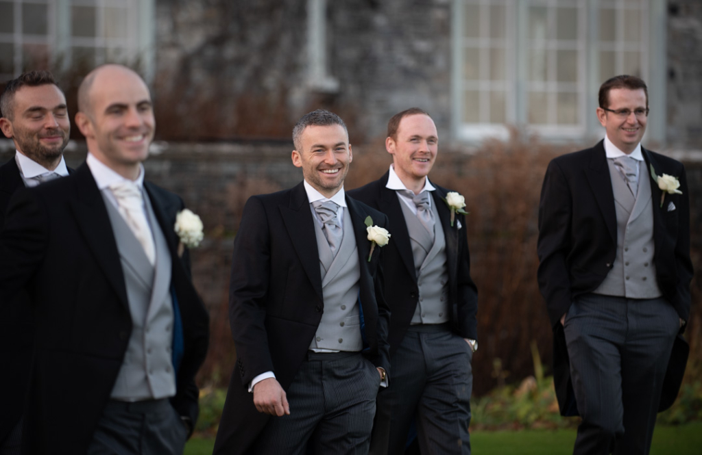 Groom and groomsmen walking and laughing together