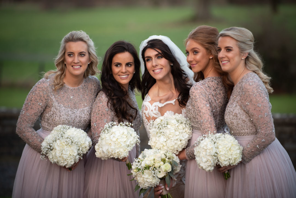 Bride in white and bridesmaids in pink dresses holding their white hydrangea flower bouquets