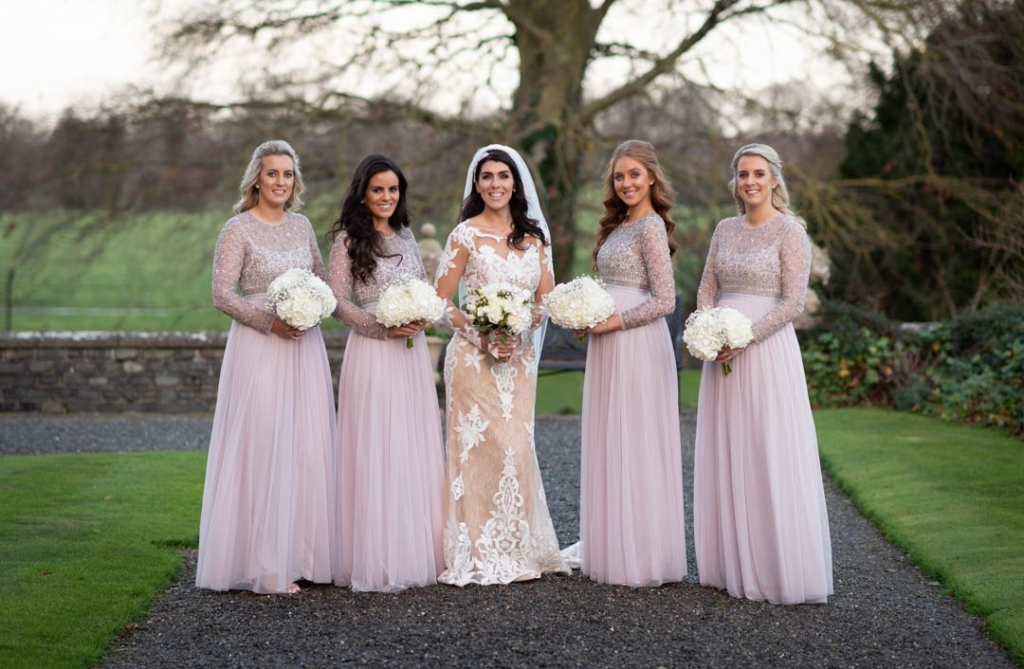 Bride and bridesmaids standing and smiling together outside on the grounds of Luttrellstown Castle