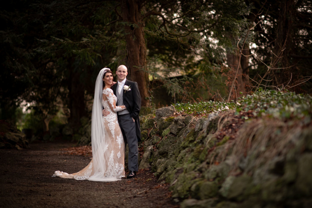 Bride and groom standing by stone wall on the Luttrellstown Castle grounds