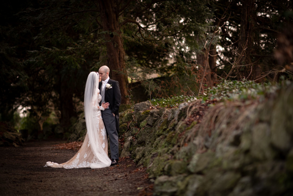 Bride and groom kissing by a stone wall at Luttrellstown Castle