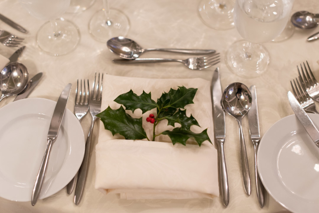 Dinner place setting with holly leaves and red berries on cream napkin