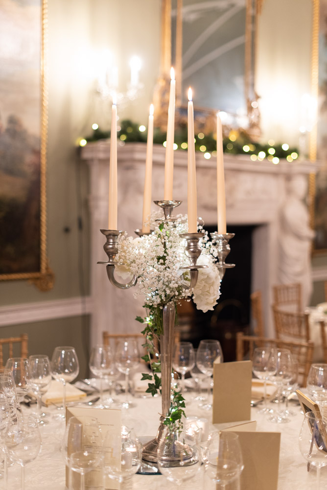 Silver candelabra in the centre of the table with cream candles and white flowers