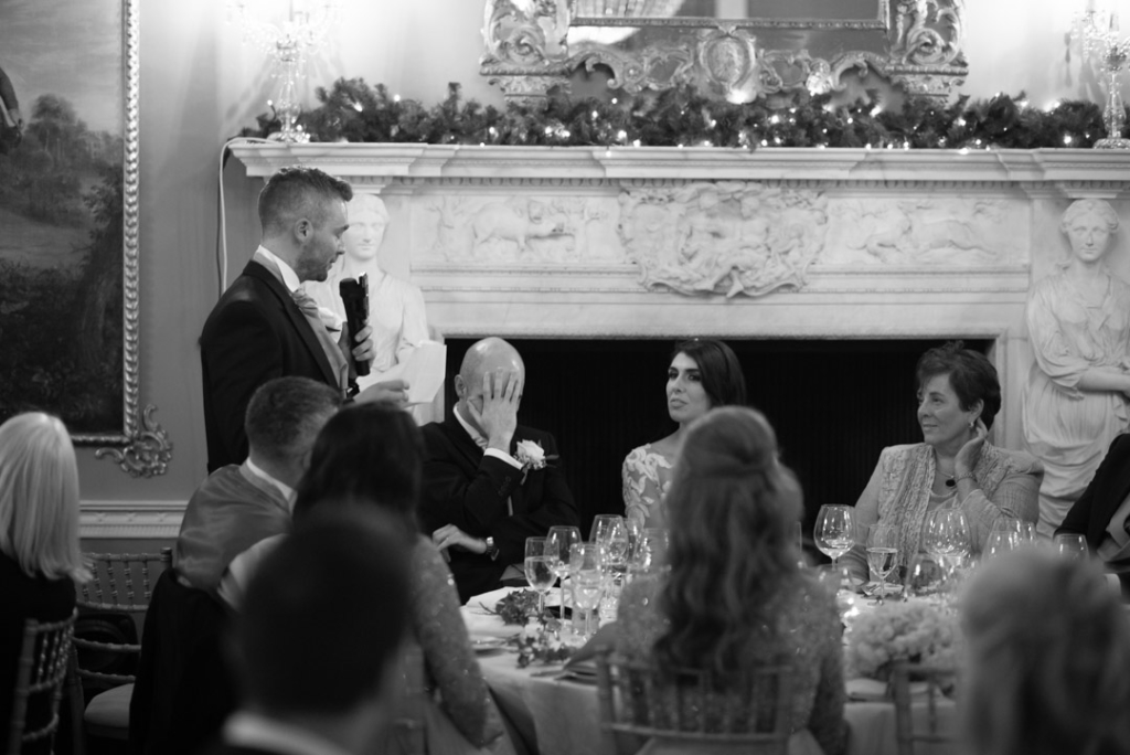 Best man giving speech while groom holds his own head in his hands
