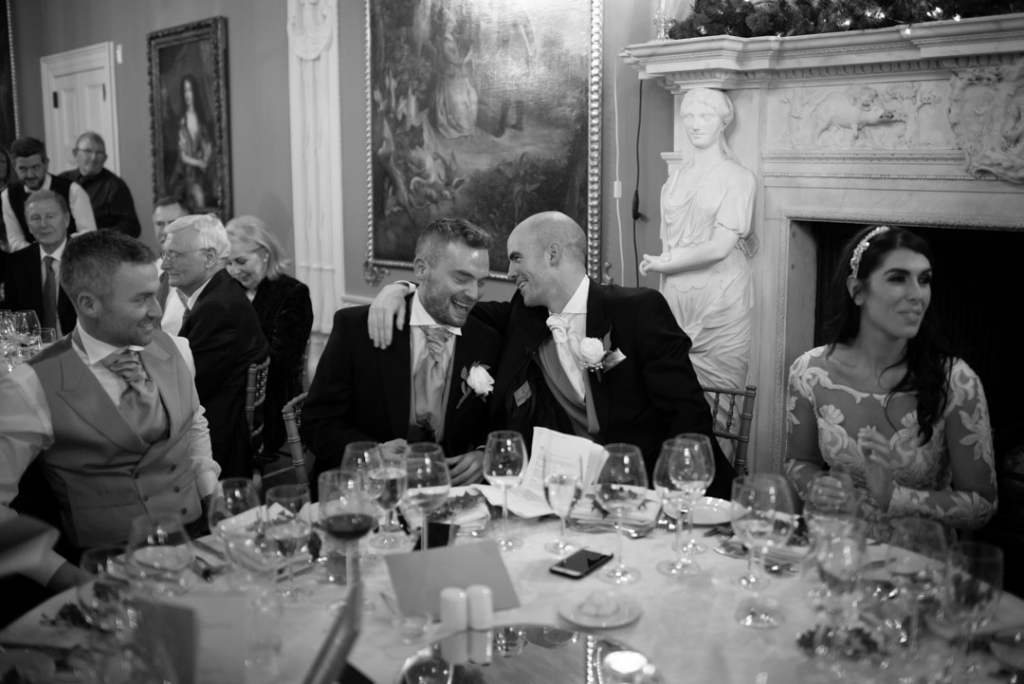 Groom and best man laughing together at the top table