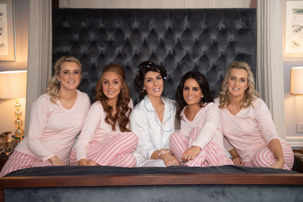 Bride and bridesmaids sitting on bed at Luttrellstown Castle