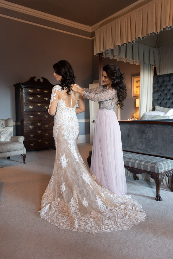 Bridesmaid closing the buttons on the back of the Brides dress in the Bridal suite at Luttrellstown Castle