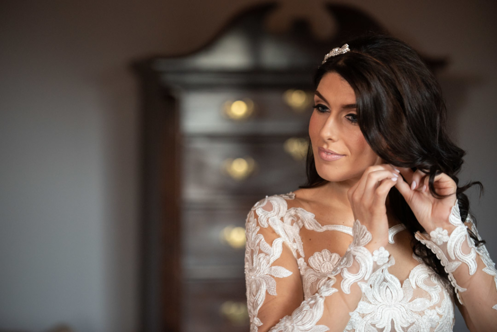 Bride putting her earrings on in the Luttrellstown Castle bridal suite