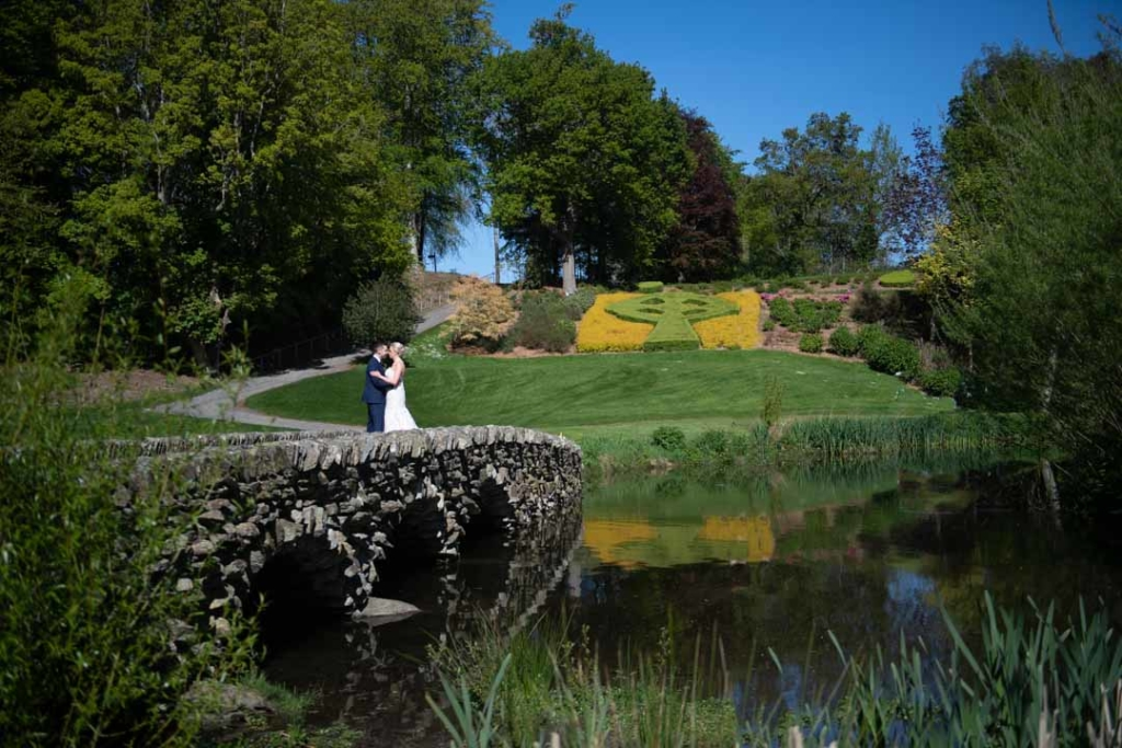 Bride and groom standing on a stone bridge in the gardens of the Druids Glen wedding venue