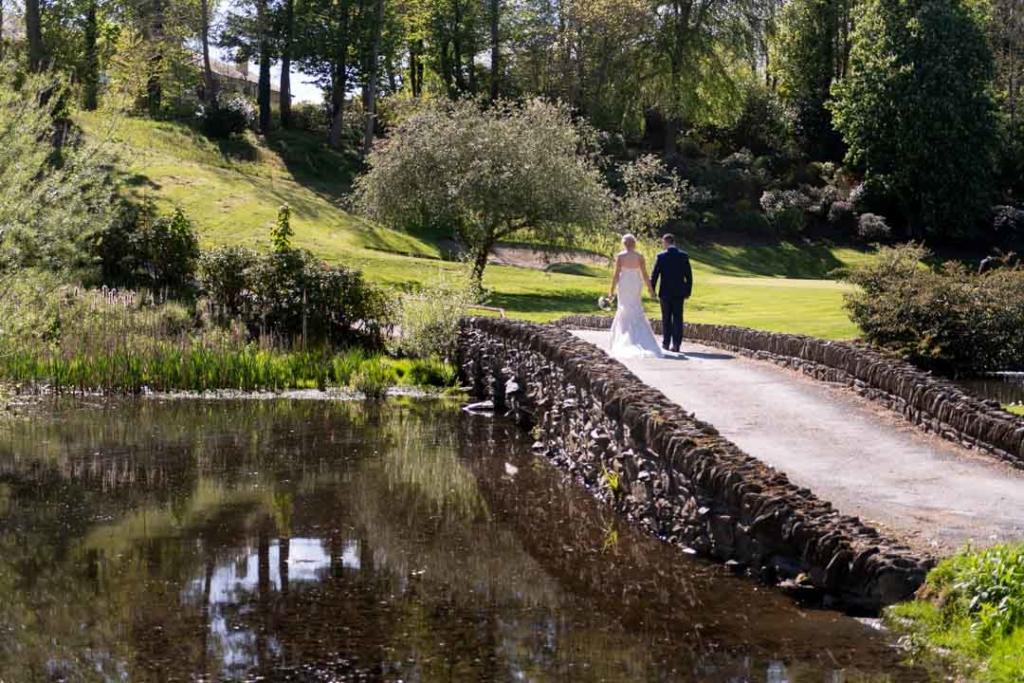 Bride and groom walking on a stone bridge in the gardens of Druids Glen