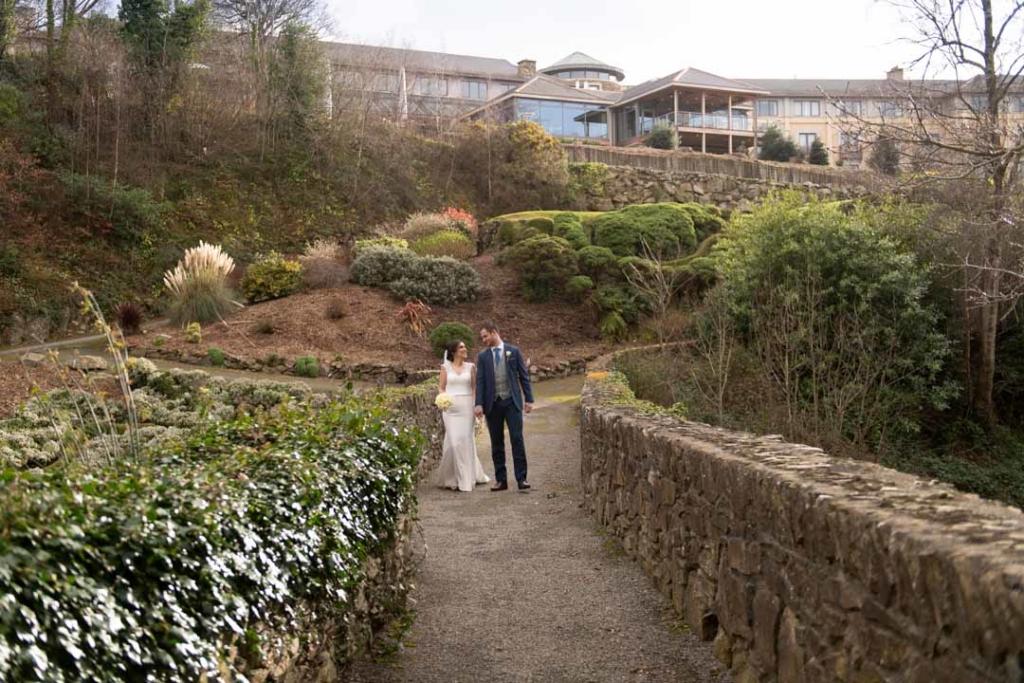 Bride and groom walking across the bridge at the Druids Glen wedding venue in Ireland