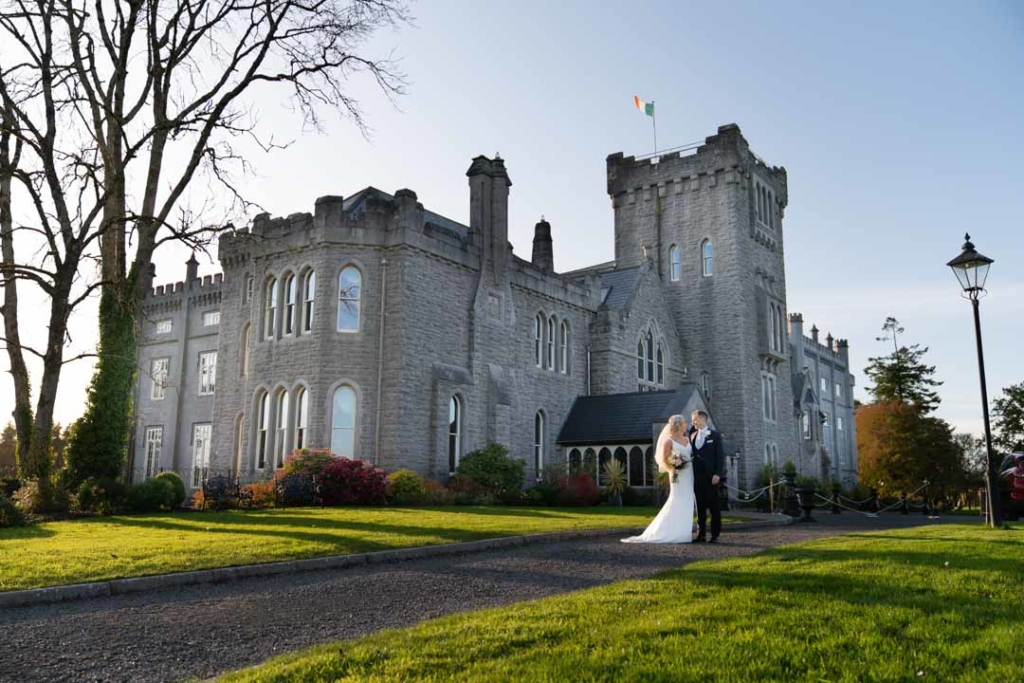 Bride and groom standing in front of their wedding venue at Kilronan Castle in Ireland