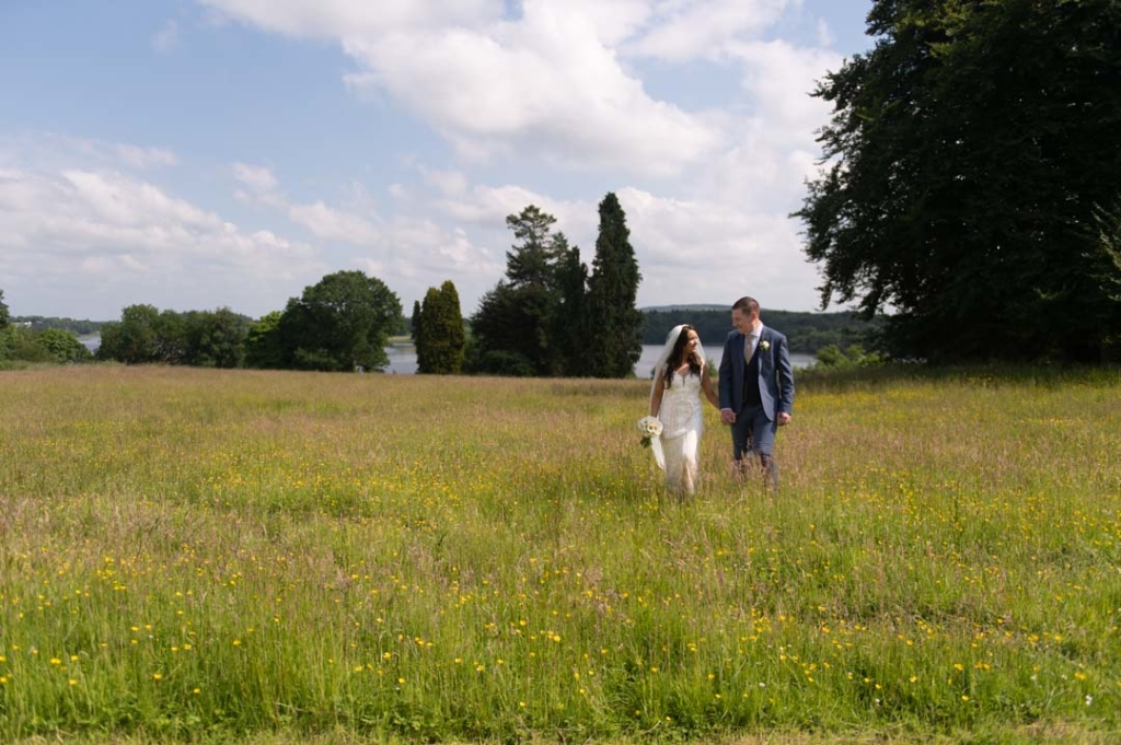 Bride and groom walking through the grass full of wild flowers at Kilronan Castle