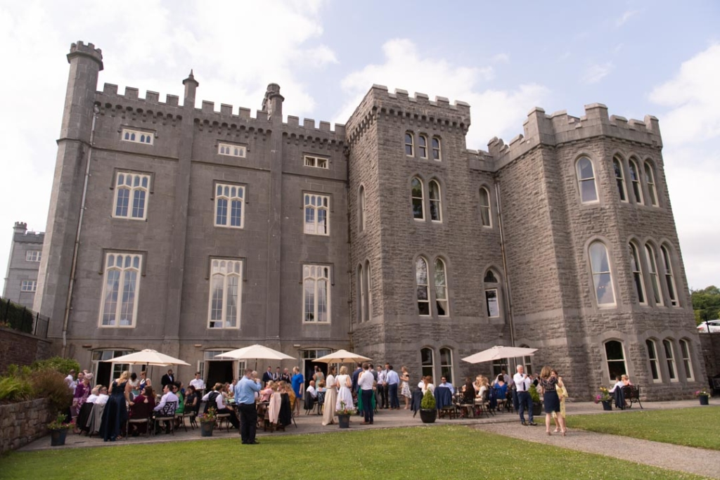 The wedding guests outside at the drinks reception with the Kilronan Castle in the background