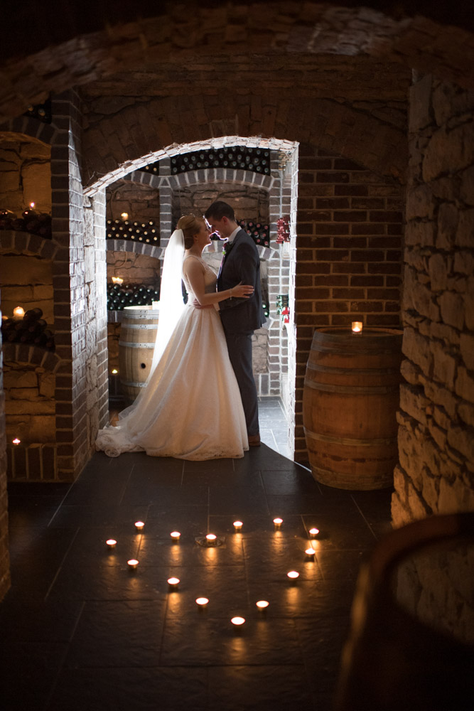 The bride and groom in the wine cellar surrounded by lit candles at the Kilronan Castle venue