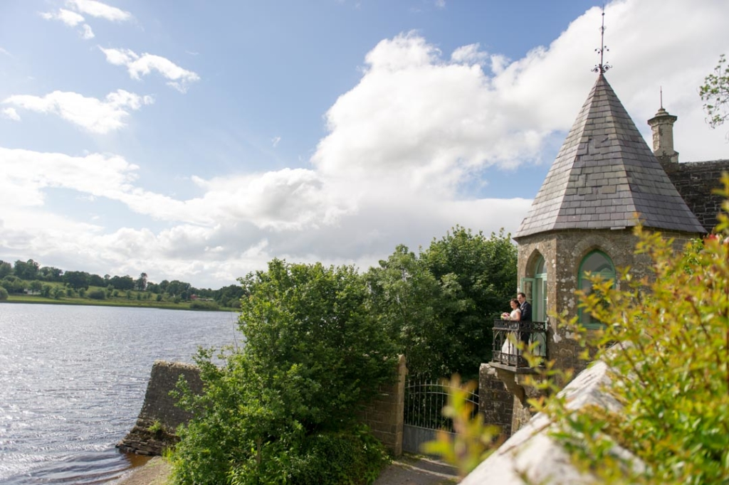 Bride and groom standing on the Castle balcony overlooking the lake at Lough Rynn Castle