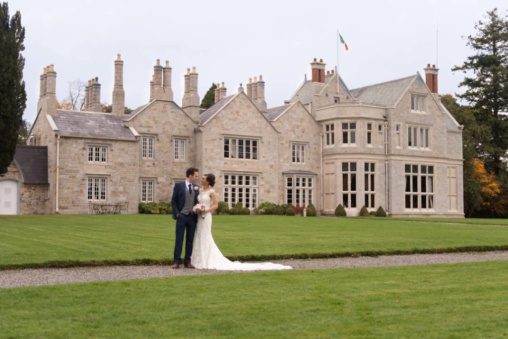 Bride and groom standing in front of the Lough Rynn Castle wedding venue in Ireland
