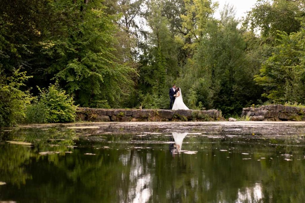 Bride and groom standing at the lake at the Lyrath Estate in Ireland