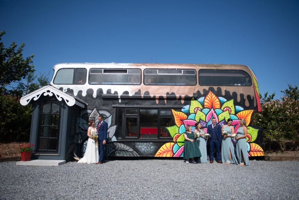 The bride and groom and their bridal party standing outside the bus accommodation at the Mount Druid alternative wedding venue