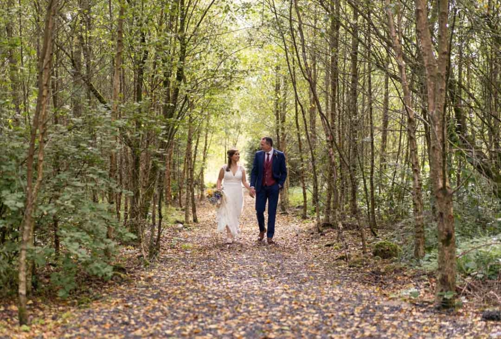 Bride and groom walking through the woodland at Mount Druid