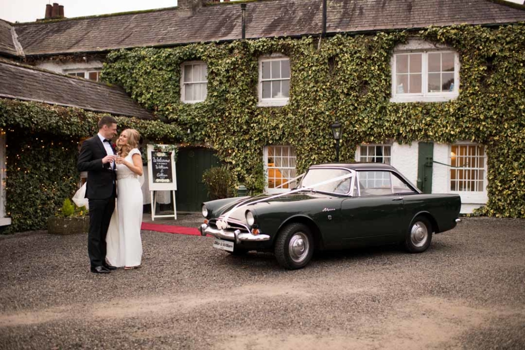 Bride and groom standing beside their green mg wedding car outside the entrance to Rathsallagh House wedding venue