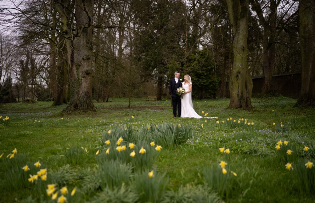 Bride and groom standing on the grass surrounded by yellow daffodils at Rathsallgh House
