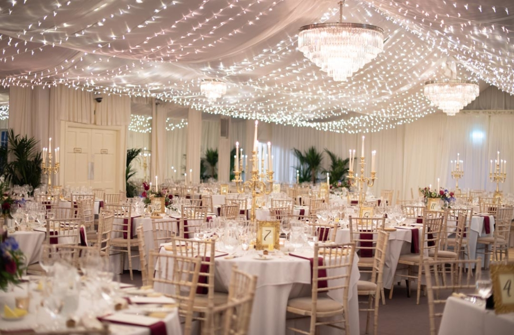 The wedding reception room set up for dinner with fairy lights on the ceiling at the Rathsallagh House wedding venue in Ireland