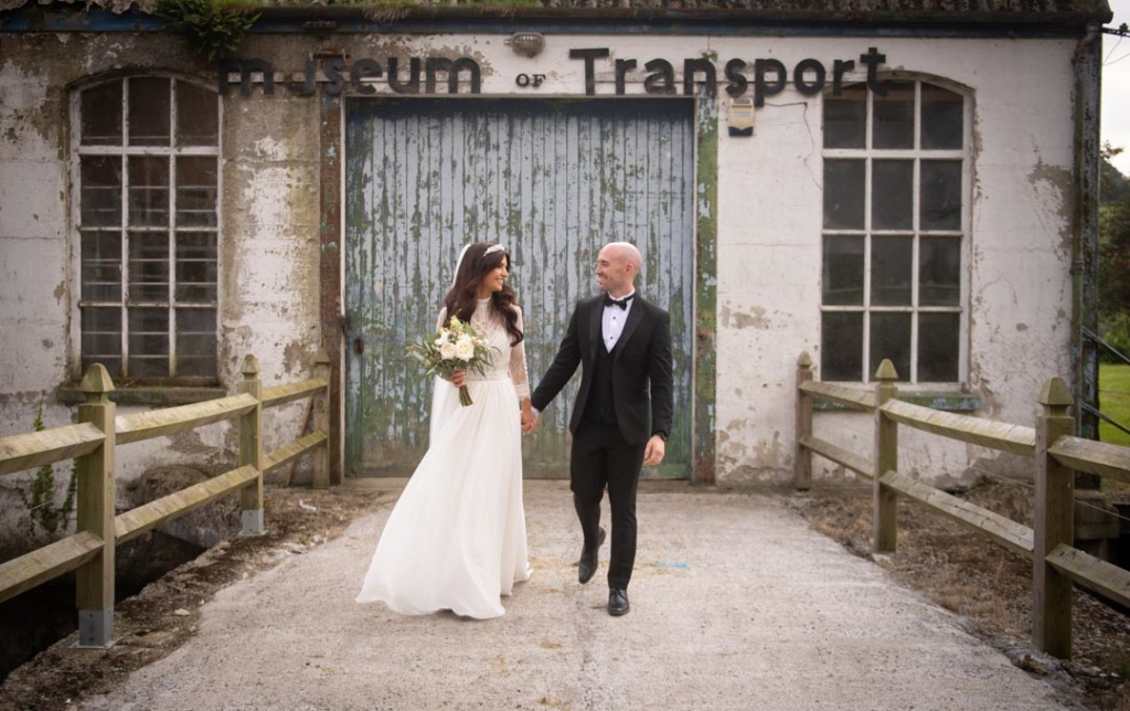 Bride and groom holding hands walking in front of the blue vintage garage door at the Mill House Slane wedding venue