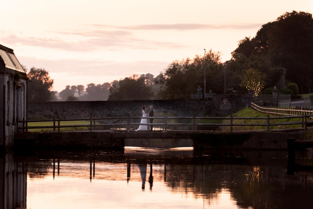 Bride and groom standing on the bridge over the river at the Mill House Slane at sunset