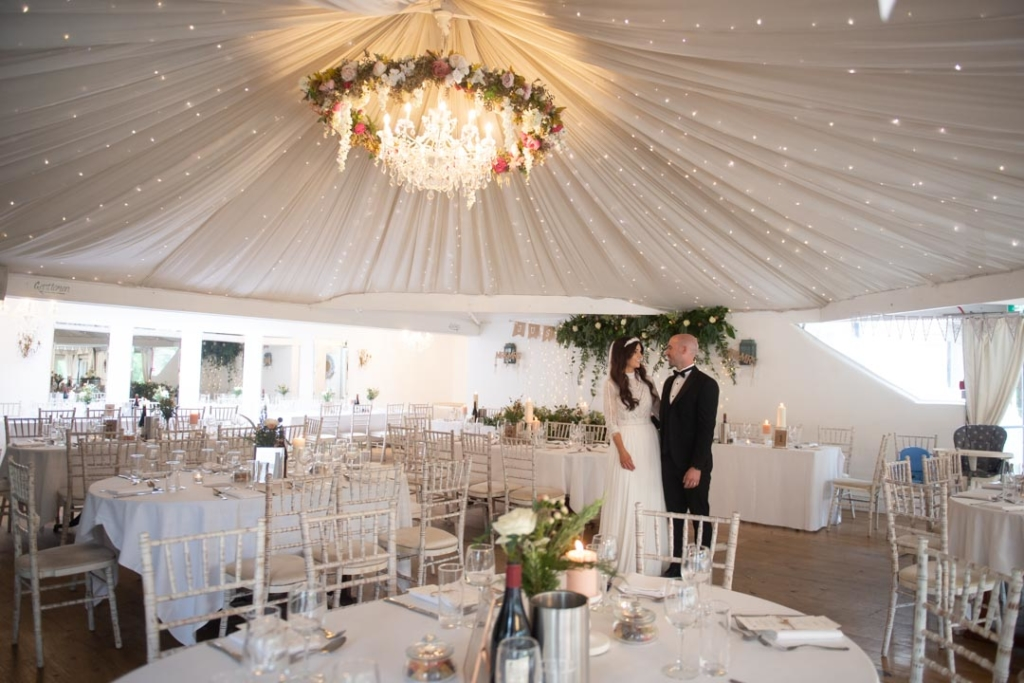 The bride and groom standing together in the marquee at the Mill House Slane