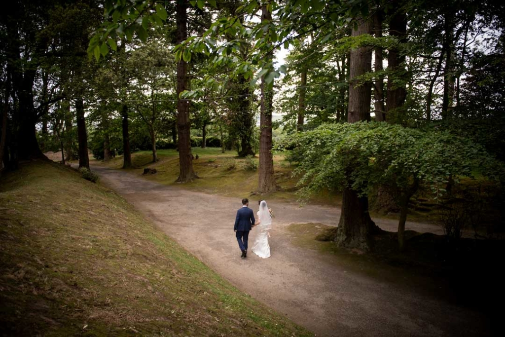 Bride and groom walking through the forest at the Tinakilly House wedding venue in Ireland