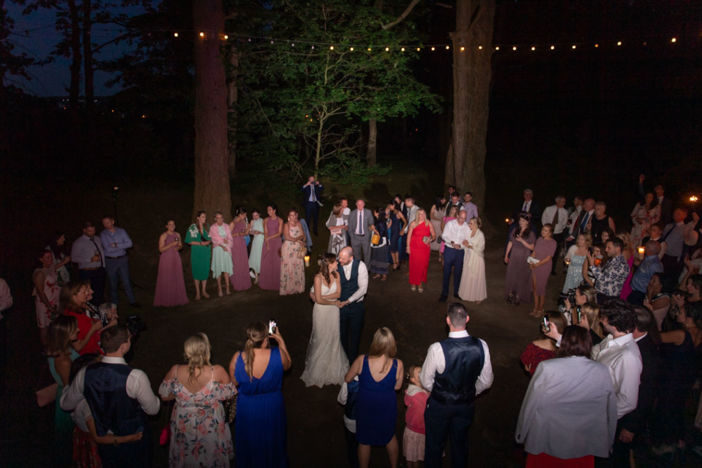 Bride and groom dancing their first dance surrounded by their guests at night time in the forest at Tinakilly House
