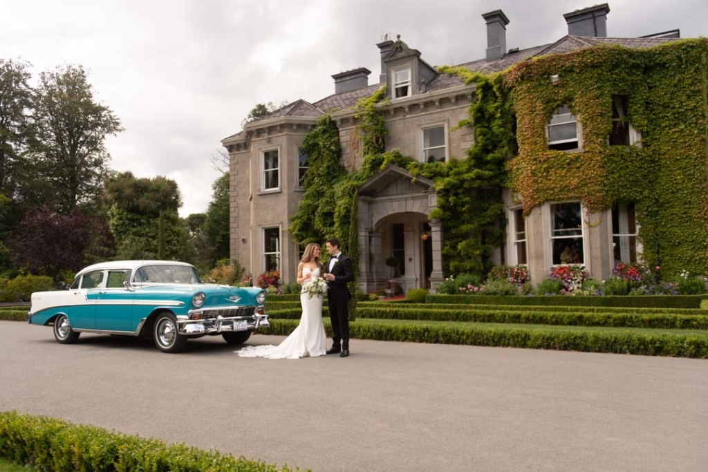 Bride and groom standing beside their blue vintage corvette wedding car in front of one of the best wedding venues in Ireland, Tinakilly House