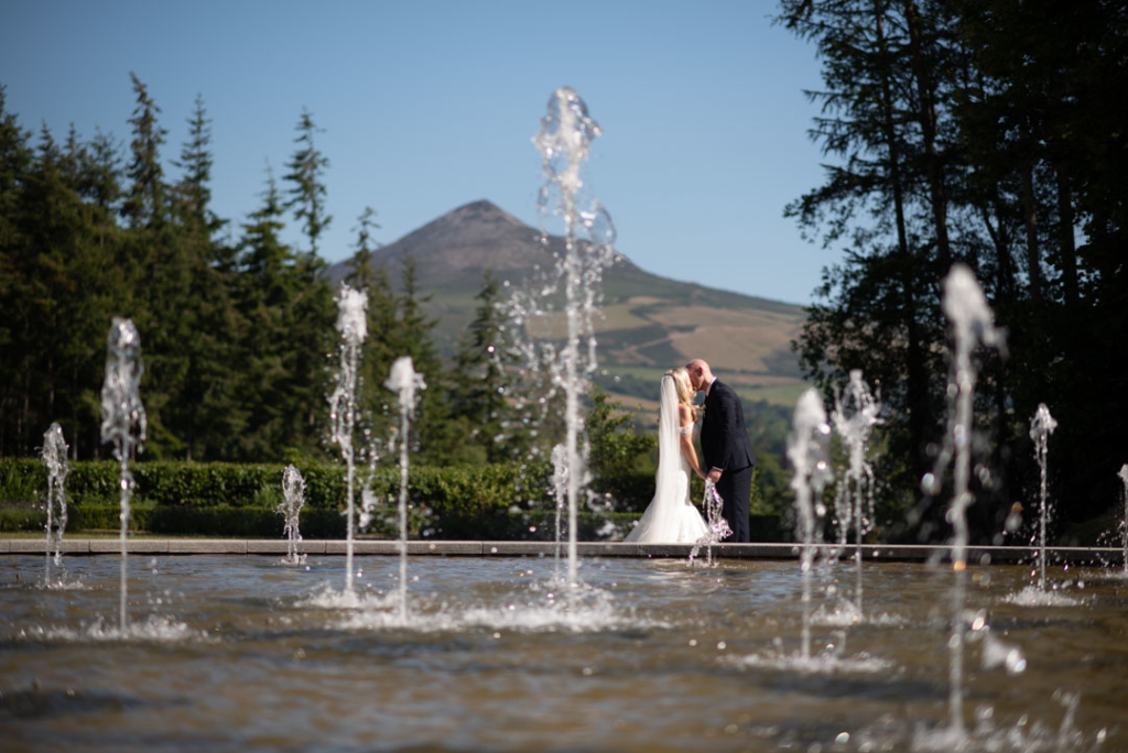 couple kissing with a water fountain in the foreground and the sugar loaf in the background