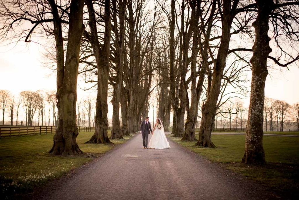 Bride and groom walking down the driveway that is lined by trees at the Tankardstown House wedding venue