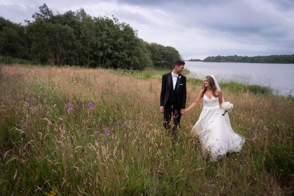 Bride and groom walking through wild meadow and grass at Virginia Park Lodge in Cavan