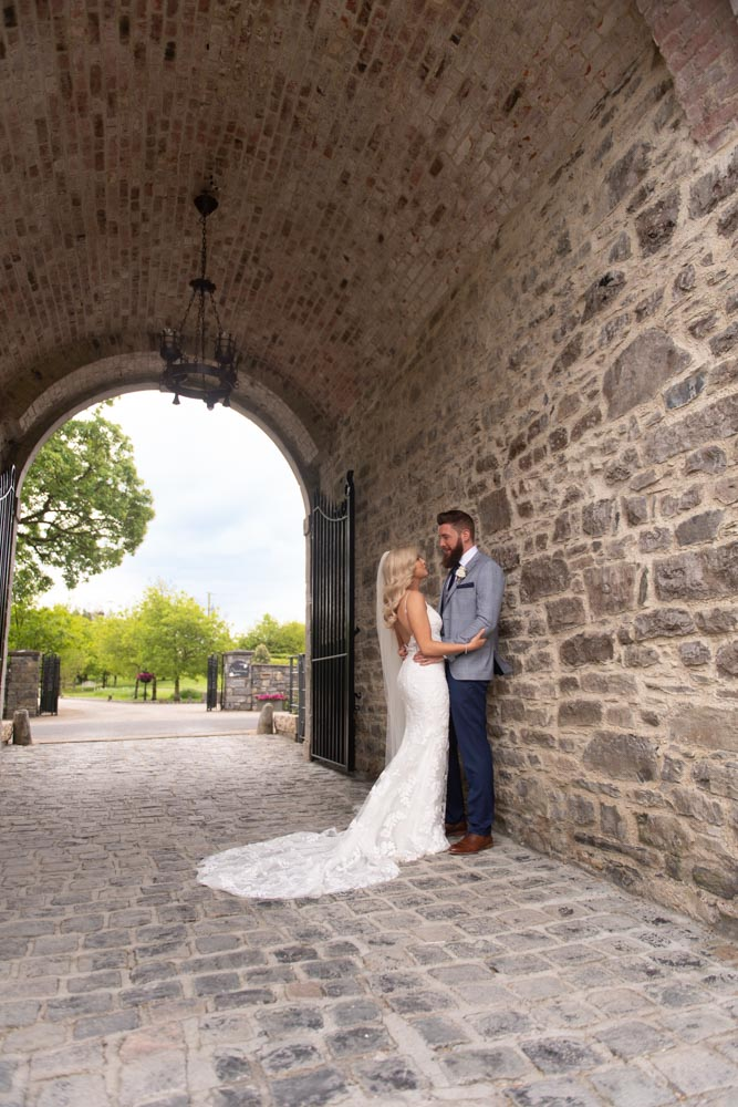 Bride and groom standing in the stone archway at the Clonabreany House venue